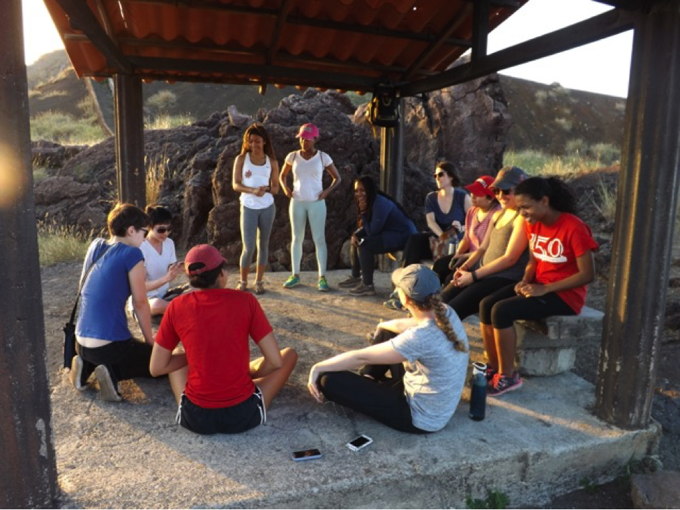 Students engaging in reflection at the base of a volcano